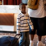 A boy pulls suitcase into conference space
